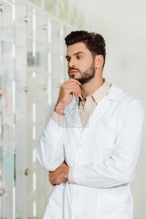 Photo pour Pharmacien réfléchi regardant vitrine dans la pharmacie - image libre de droit
