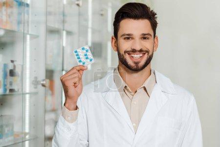 Photo pour Beau pharmacien souriant à la caméra tout en tenant blister avec des pilules - image libre de droit