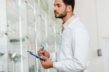 Photo pour Vue latérale du beau pharmacien avec presse-papiers regardant la vitrine de la pharmacie - image libre de droit