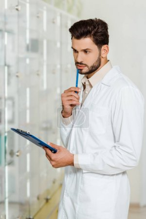 Photo for Pensive pharmacist with clipboard and pen in drugstore - Royalty Free Image
