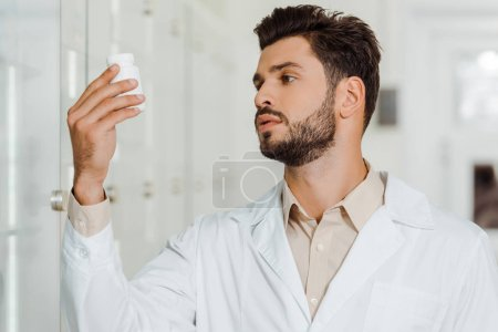 Photo for Druggist in white coat looking at jar with pills in pharmacy - Royalty Free Image
