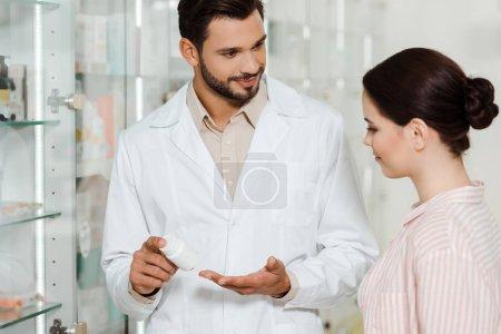 Photo pour Pharmacien souriant montrant un pot contenant un médicament au client par pharmacie vitrine - image libre de droit