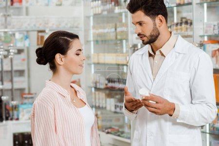 Photo pour Vue latérale du pharmacien montrant au bocal du client des pilules par la vitrine de la pharmacie - image libre de droit