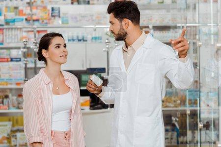 Photo pour Drogue tenant un pot de pilules et pointant vers la vitrine du client - image libre de droit