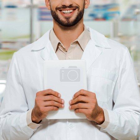 Photo pour Vue croustillante d'un pharmacien souriant en manteau blanc tenant une tablette numérique - image libre de droit
