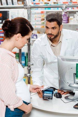Photo pour Une pharmacienne regarde une femme enceinte payante dans une pharmacie - image libre de droit