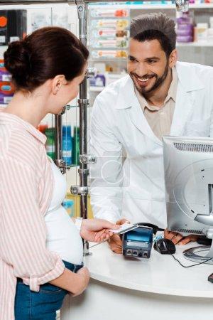 Photo pour Une cliente enceinte qui paie avec sa carte de crédit et qui sourit à un toxicomane au comptoir - image libre de droit
