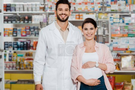 Foto de Smiling pharmacist and pregnant woman looking at camera with pharmacy showcase at background. - Imagen libre de derechos