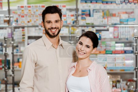Photo for Smiling customers looking at camera with medicaments on pharmacy showcase at background - Royalty Free Image