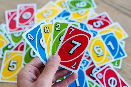 Photo pour KYIV, UKRAINE - 22 NOVEMBRE 2019 : vue recadrée de l'homme tenant des cartes à jouer uno colorées - image libre de droit