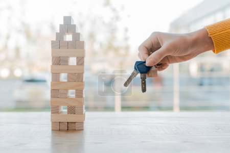 Photo for KYIV, UKRAINE - NOVEMBER 22, 2019: cropped view of woman holding keys blocks wood tower game - Royalty Free Image
