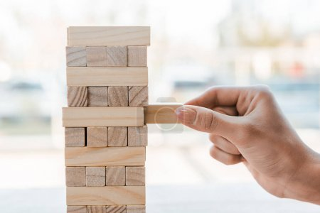 KYIV, UKRAINE - NOVEMBER 22, 2019: cropped view of woman playing blocks wood game at home