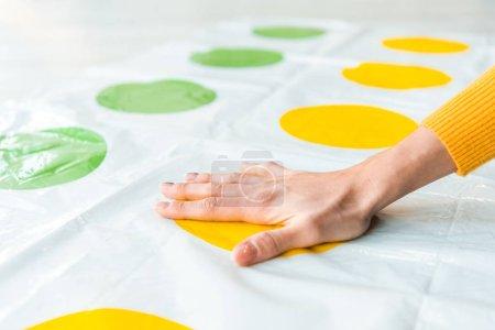Foto de KYIV, UCRANIA - 22 de noviembre de 2019: vista recortada de la mujer poniendo la mano en el círculo amarillo mientras juega al twister game - Imagen libre de derechos