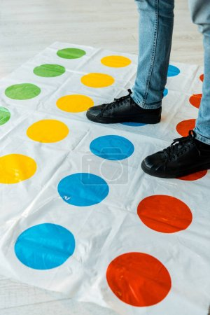 KYIV, UKRAINE - NOVEMBER 22, 2019: cropped view of man in jeans standing on twister game