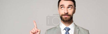 Photo pour Prise de vue panoramique d'un homme d'affaires souriant détournant les yeux tout en montrant un geste d'idée isolé sur gris - image libre de droit