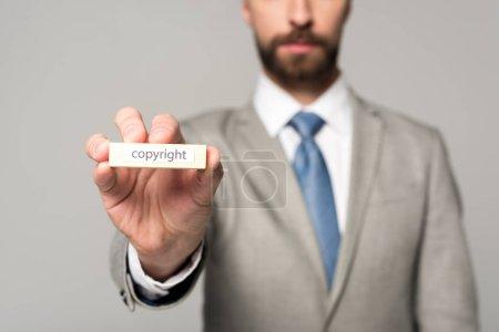 Photo pour Vue partielle de l'homme d'affaires montrant bloc de bois avec copyright mot isolé sur gris - image libre de droit