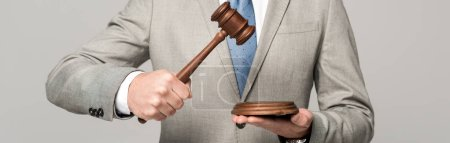 Photo pour Vue partielle du juge tenant le marteau isolé sur gris, photo panoramique - image libre de droit