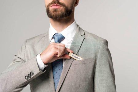 Photo pour Vue partielle de l'homme d'affaires mettant bloc de bois avec droit d'auteur mot dans poche isolé sur gris - image libre de droit