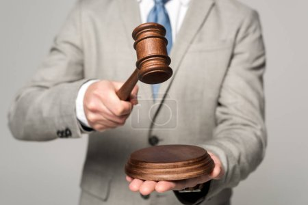 Photo pour Vue partielle du juge tenant le marteau isolé sur gris - image libre de droit
