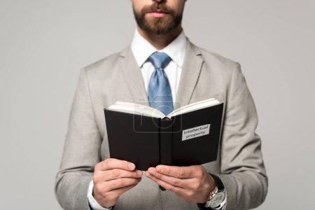 Photo pour Vue recadrée du livre de lecture de l'homme d'affaires avec titre de propriété intellectuelle isolé sur gris - image libre de droit