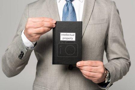 Photo pour Vue partielle de l'homme d'affaires détenant un livre juridique avec titre de propriété intellectuelle isolé sur gris - image libre de droit