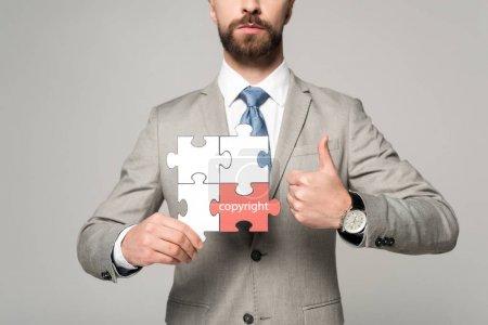 Foto de La vista recortada del hombre de negocios que sostiene rompecabezas de jigsaw con la carta de derechos de autor y mostrando pulgar aislado en gris. - Imagen libre de derechos
