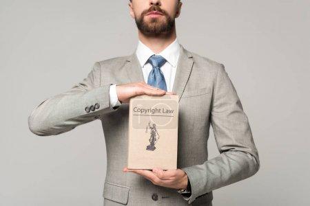 Photo pour Vue partielle d'un avocat détenant un livre avec titre de droit d'auteur isolé sur gris - image libre de droit