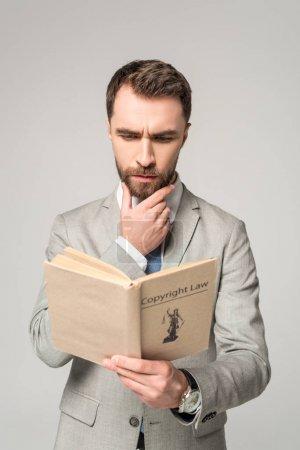 Photo pour Livre de lecture d'un avocat sérieux avec titre de droit d'auteur isolé sur gris - image libre de droit