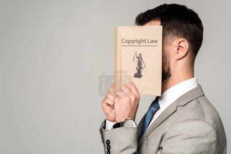 Photo pour Vue de côté de l'avocat masquant le visage d'un livre sur le droit d'auteur isolé sur gris - image libre de droit