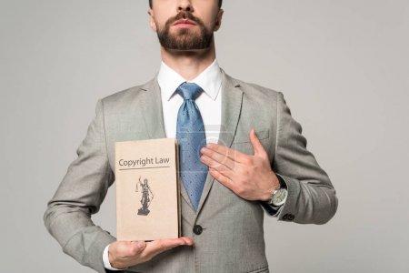 Photo pour Vue partielle d'un avocat tenant la main près du cœur et livre avec un titre de droit d'auteur isolé sur gris - image libre de droit