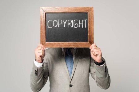 Photo pour Homme d'affaires obscurcissant visage avec tableau noir avec inscription de copyright isolé sur gris - image libre de droit