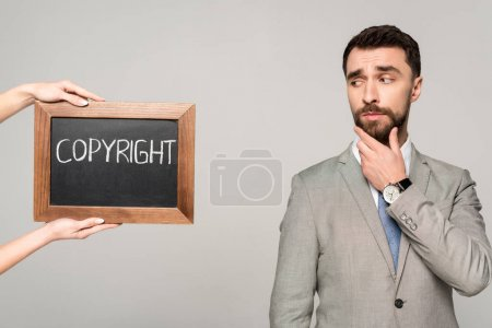 partial view of woman holding chalkboard with copyright inscription near skeptical businessman isolated on grey