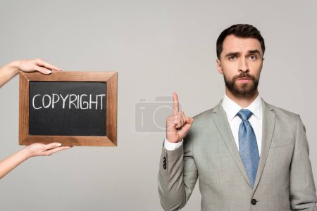 Photo for Partial view of woman holding chalkboard with copyright inscription near businessman showing idea sign isolated on grey - Royalty Free Image