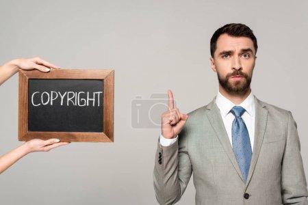 Photo pour Vue partielle de la femme tenant un tableau avec inscription de copyright près de l'homme d'affaires montrant le signe d'idée isolé sur gris - image libre de droit
