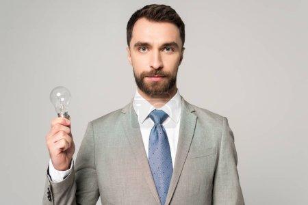 Photo pour Homme d'affaires confiant tenant ampoule et regardant la caméra isolée sur gris - image libre de droit