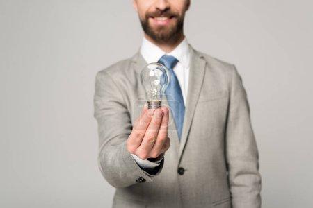 Photo pour Vue partielle d'un homme d'affaires souriant tenant une ampoule isolée sur le gris - image libre de droit