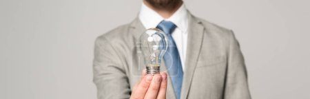 Photo for Cropped view of businessman holding light bulb isolated on grey, panoramic shot - Royalty Free Image