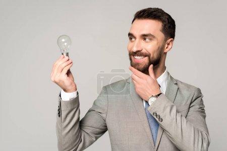 Foto de Sonriente empresario tocando la cara mientras mantiene la bombilla aislada sobre gris. - Imagen libre de derechos