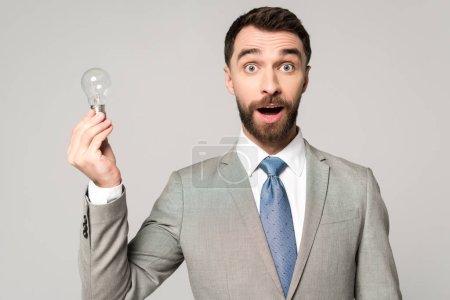 Photo pour Excité homme d'affaires tenant ampoule et regardant caméra isolé sur gris - image libre de droit