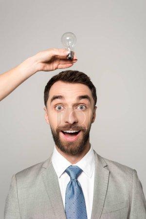 Photo pour Vue en coupe d'une femme tenant une ampoule électrique au-dessus de la tête d'un homme d'affaires excité isolé sur gris - image libre de droit