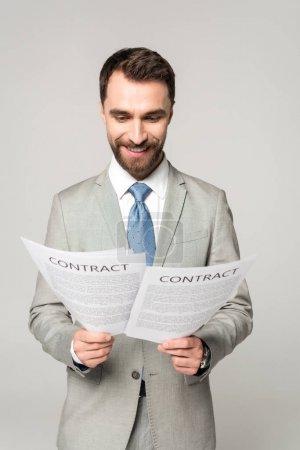 Photo pour Beau homme d'affaires lisant des contrats et souriant isolé sur gris - image libre de droit