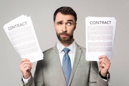 Photo pour Un homme d'affaires sceptique qui détient des contrats et regarde ailleurs isolé sur le gris - image libre de droit