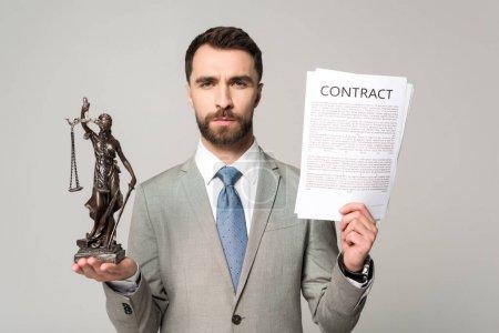 Photo pour Un avocat confiant détenant un contrat et une statue en regardant une caméra isolée sur gris - image libre de droit