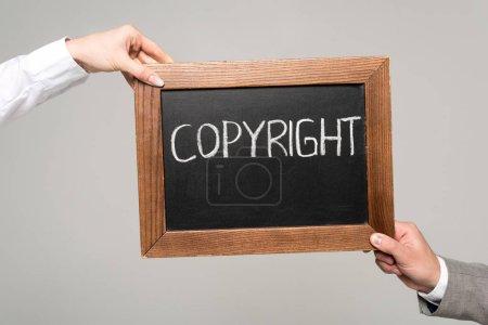 Foto de Vista recortada de empresarios que sostienen pizarra con inscripción de derechos de autor aislada en gris - Imagen libre de derechos
