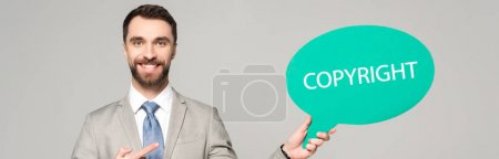 Photo for Panoramic shot of smiling businessman pointing with finger at thought bubble with copyright inscription isolated on grey - Royalty Free Image
