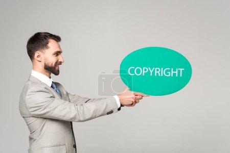 Photo pour Vue latérale d'un homme d'affaires souriant tenant une bulle de pensée avec inscription de copyright isolée sur gris - image libre de droit
