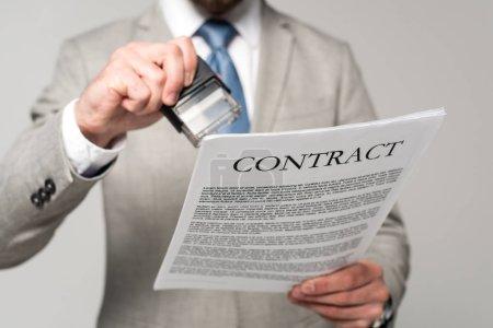 Photo pour Vue recadrée de l'homme d'affaires mettant timbre sur contrat isolé sur gris - image libre de droit