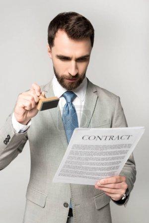 Photo pour Un avocat sérieux appose son sceau sur un contrat isolé sur gris - image libre de droit