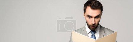 Photo pour Prise de vue panoramique d'homme d'affaires choqué regardant des documents dans un dossier papier isolé sur gris - image libre de droit