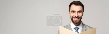 Photo for Panoramic shot of positive businessman smiling at camera while holding paper folder isolated on grey - Royalty Free Image